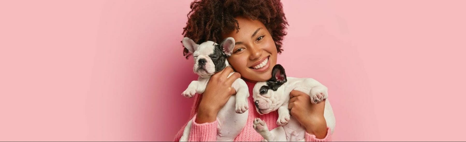 Woman holding two puppies